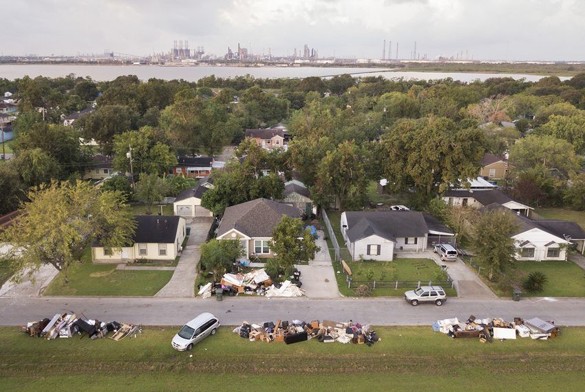 Motiva, the largestcrude oilrefinery in the United States, can be seen in the distance from Port Arthur on Wednesday, Sept. 20, 2017. Flood-damaged debris is piled outside of homes in the foreground.