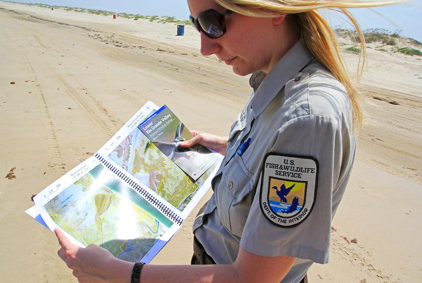 Jennifer White, a public relations liaison for the U.S. Fish and Wildlife Service, looks over a map of Boca Chica Beach in...