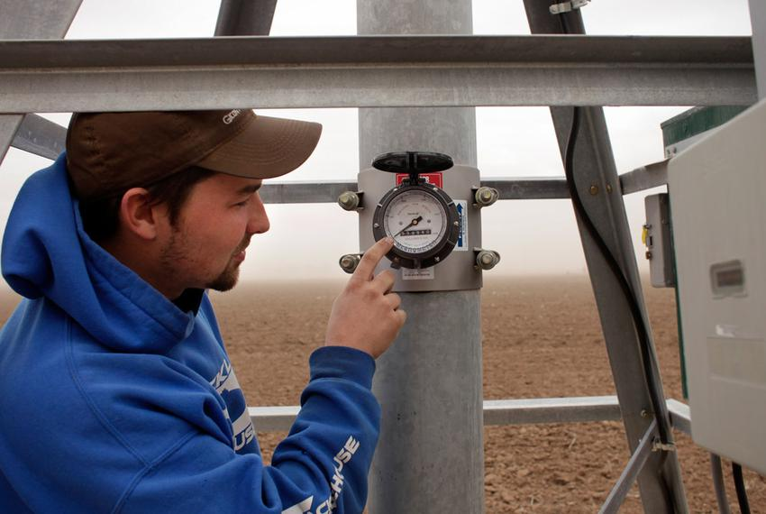 Kyle DuBois of Massey Irrigation examines a recently-installed well water meter in Lubbock, TX, on Mar. 8, 2012.