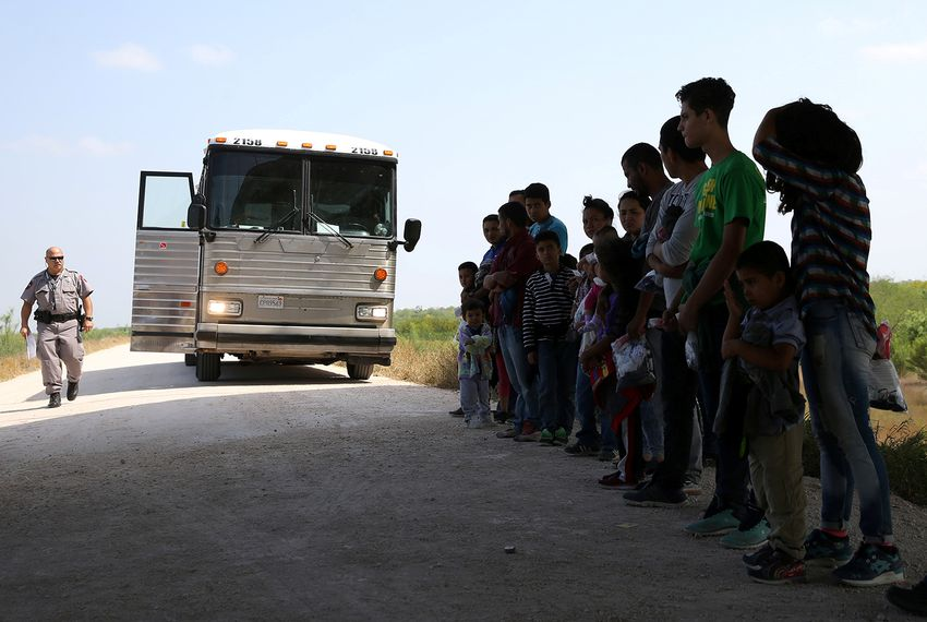 Immigrants who turned themselves in to border patrol agents after illegally crossing the border from Mexico into the U.S. wait to be transported for processing in the Rio Grande Valley sector, near McAllen, Texas, on April 2, 2018.