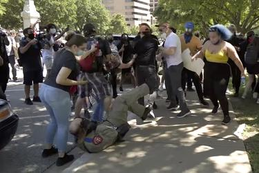 A DPS is pushed to the ground by a group of protesters during the George Floyd protest at the capitol on May 31, 2020.