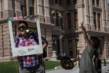 """Kate Messer poses for a picture while Kai Gadd-Shefman tosses flowers in the air following the """"Big Gay Wedding"""" ceremony that married over 40 same-sex couples on the south lawn of the Texas State Capitol in Austin on July 4, 2015."""