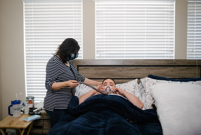 RICHMOND, TX - MARCH 3:  Mauricio Marin's wife, Daysi, helps fasten his CPAP machine as he returns to bed at their home in R…