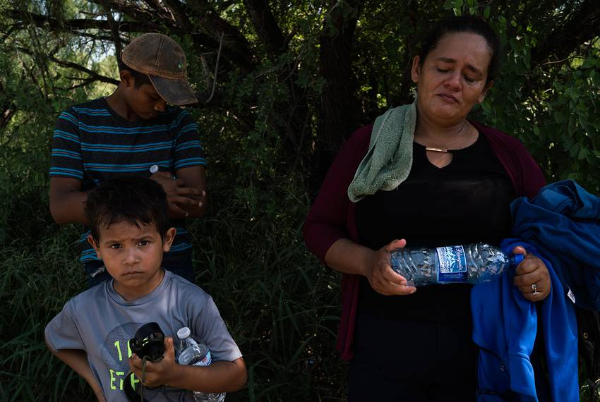 Doris Romero, 42, from Honduras, waits with her son, Jose, 14, and her nephew, Ronald, 4, wait to be processed after turni...
