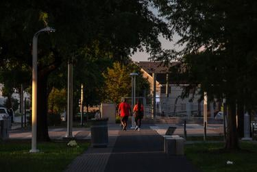 A couple holds hands during their walk around Emancipation Park in Houston, TX on June 15, 2020.