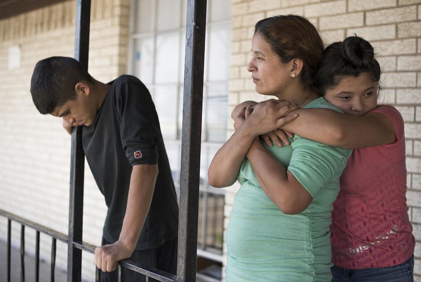 Rosa Ortega is hugged by her daughter Gracie Garza, 12. Son Rene Garza, 16, stands next to them.