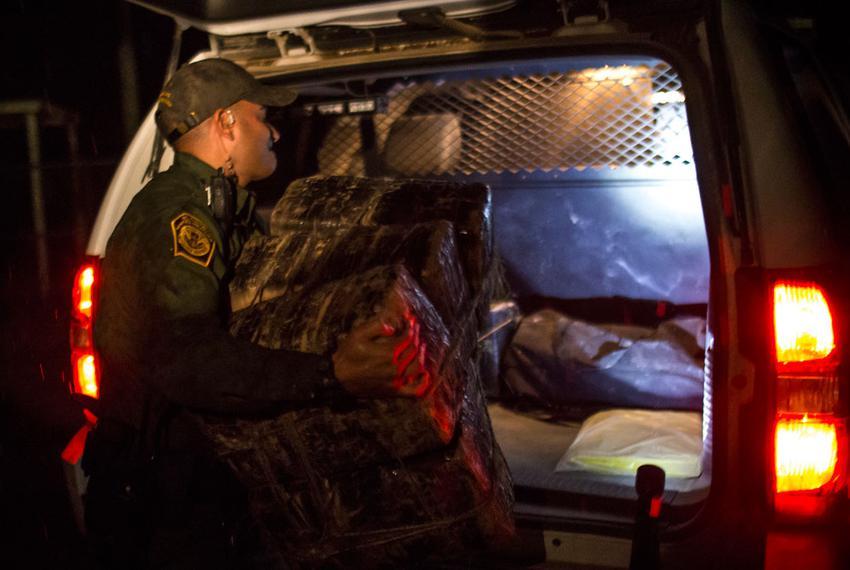 Border Patrol Agent P.J. Diaz loads a seized package of marijuana into his service vehicle.
