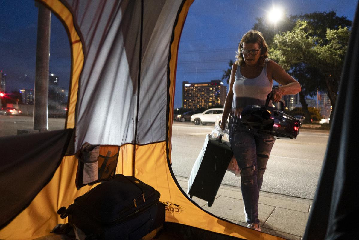 Christina Jezzizki, 58, starts preemptively moving her belongings to avoid being arrested for camping in front of Austin City Hall, but is interrupted by rain on July 10, 2021.Source diversity info: White Female