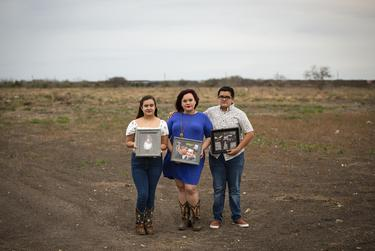 Delia Ramos, center, holds a photo of her and her husband Ricardo with her daughter, right, and son TKTKTKT. Ricardo died in July 2020. Brownsville on March 7, 2021.