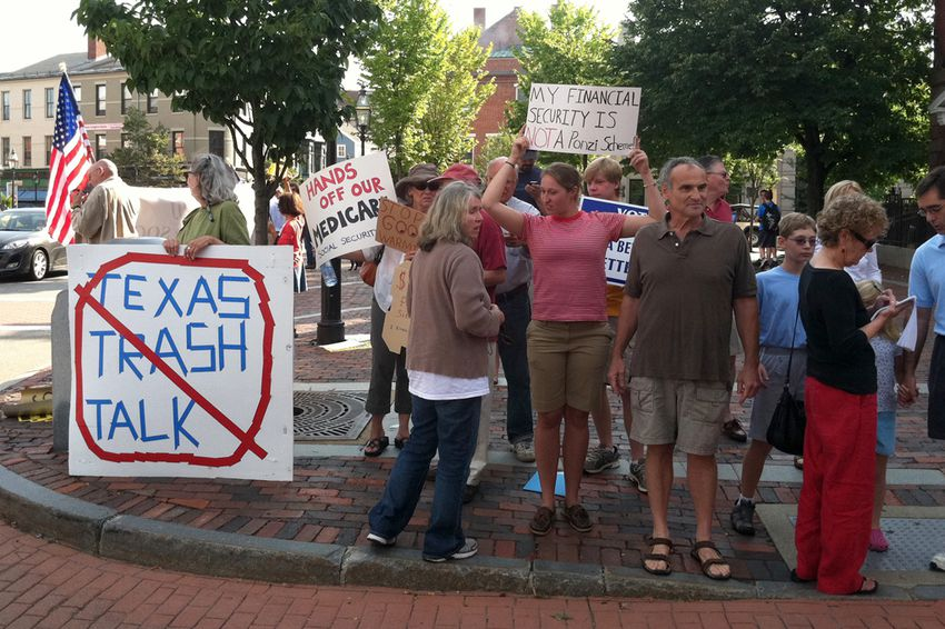 Protesters in Portsmouth await Perry's arrival at Popovers restaurant Thursday, where the Texas governor will meet with voters.