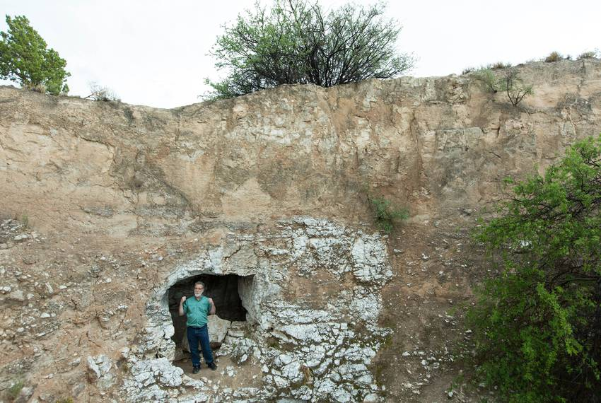 George Veni, executive director of the National Cave and Karst Research Institute, stands above a stream that flows out of...