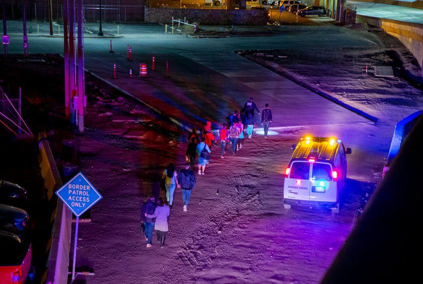 U.S. Customs and Border Protection agents escort migrants near the Paso del Norte International Bridge to a processing center in El Paso.