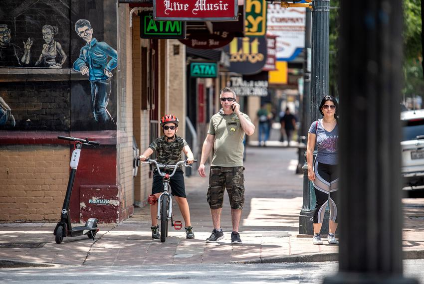 People wait to cross the street in downtown Austin on May 23, 2020.