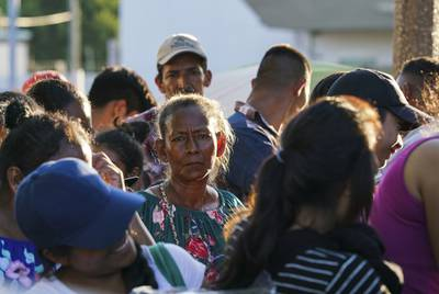 "Asylum seekers wait in line to get a meal provided by Team Brownsville near the Gateway International Bridge in Matamoros, Mexico on Sunday, Oct. 13, 2019. Most of the people have been sent back under the Migrant Protection Protocols, MPP, also known as ""Remain in Mexico"" program along with some Mexican nationals awaiting their turn to seek asylum in the U.S. Verónica G. Cárdenas for The Texas Tribune"