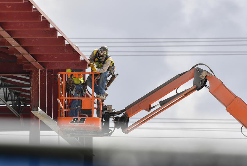 Construction workers work on an office building on the corner or Metric and Parmer in Austin on June 18, 2020.