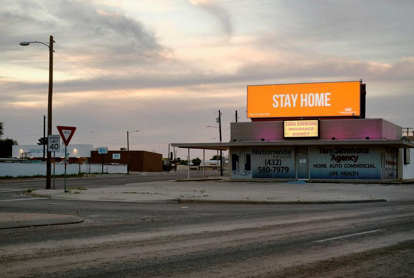 The intersection of Kermit Highway and Andrews Highway is empty as an advertisement urges the community to stay home durin...
