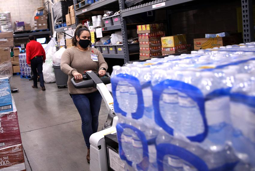 Amber Campos moves a pallet of bottled water from a semi-trailer truck at the loading dock of the H-E-B grocery store at  in…