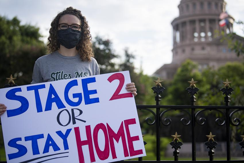 "Darcy Vogt Williams, who organized the protest, holds a sign outside the Capitol grounds in Austin during the ""Mask Up, Line…"