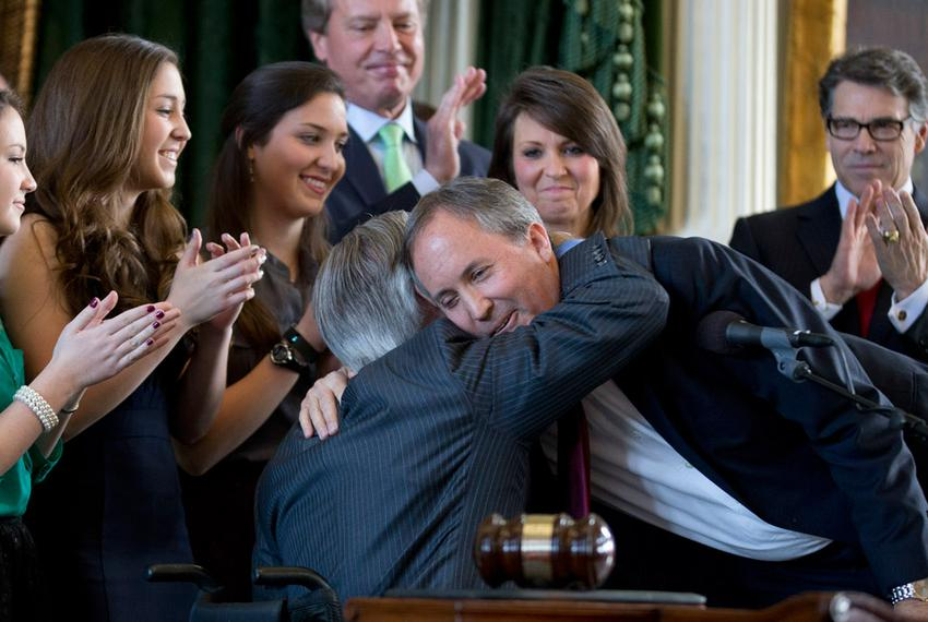 Gov. Rick Perry, right, and Lt. Gov. David Dewhurst, back, watch as outgoing Attorney General Greg Abbott welcomes new Att...