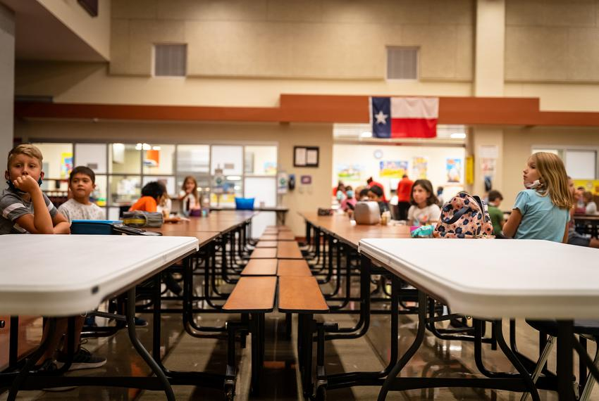 Students sit at socially distance intervals in the lunch room at Jacob's Well Elementary School in Wimberley on Sept 4, 2020.