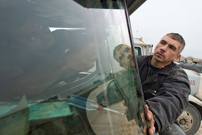 Eddie Posselt (right) works on a 18 Wheeler tanker truck's windshield with his employee Danilo Estaco (inside truck) on Dec. 12, 2013. Posselt moved to Carrizo Springs last year to work in the oil fields, ended up launching Windshields Etc in July. He now runs the business full time.  The oil drilling boom in South Texas' Eagle Ford Shale has also led to a boom in windshield repair and replacement.