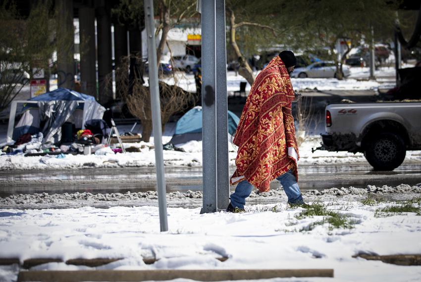 A person walks past tents near the Interstate-35 frontage road  in Austin on Feb.16, 2021. A winter storm caused icy roads a…