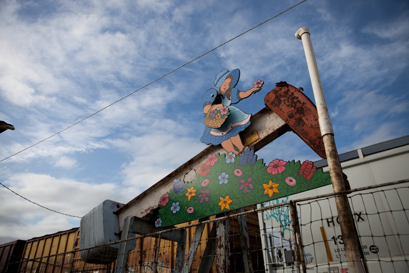 """Near a Chevron station, the vibrant colors of this installation — """"Girl Picking Flowers"""" — clash with the rusty pump jack it clings to."""