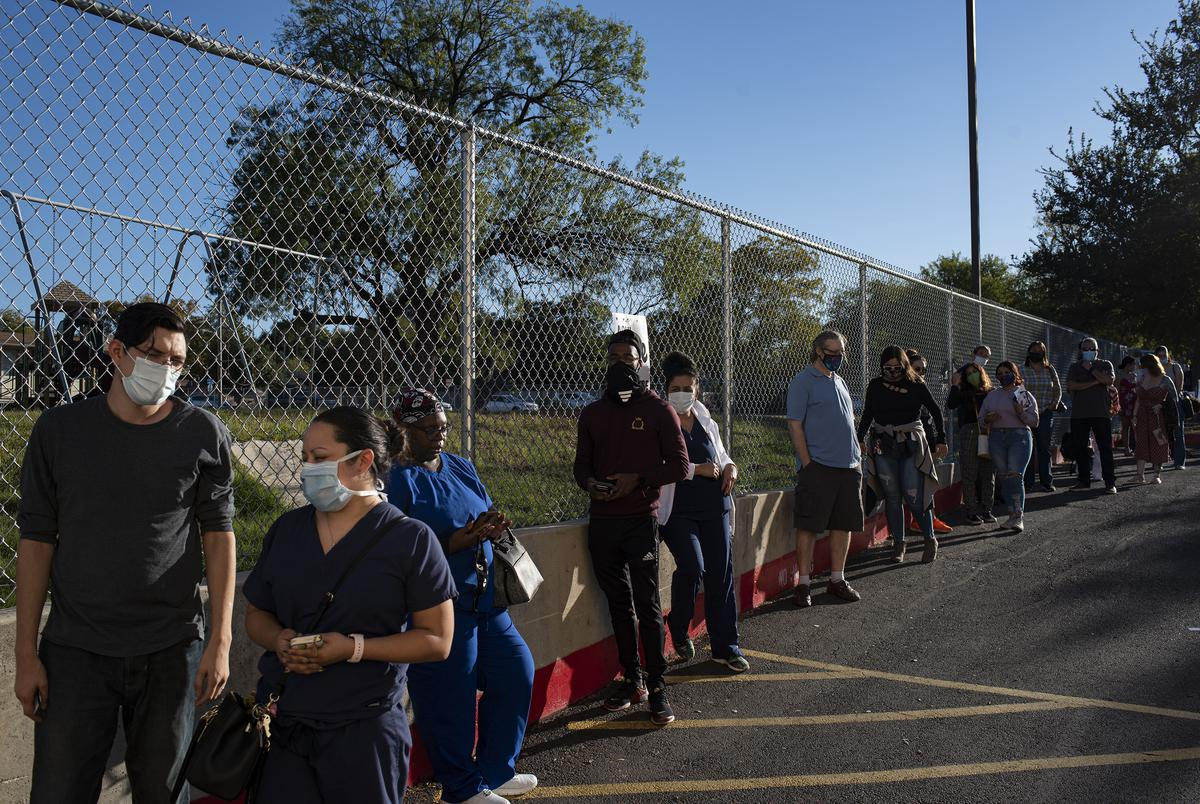 Voters wait in line outside Cody Public Library in San Antonio during the evening hours of Election Day.