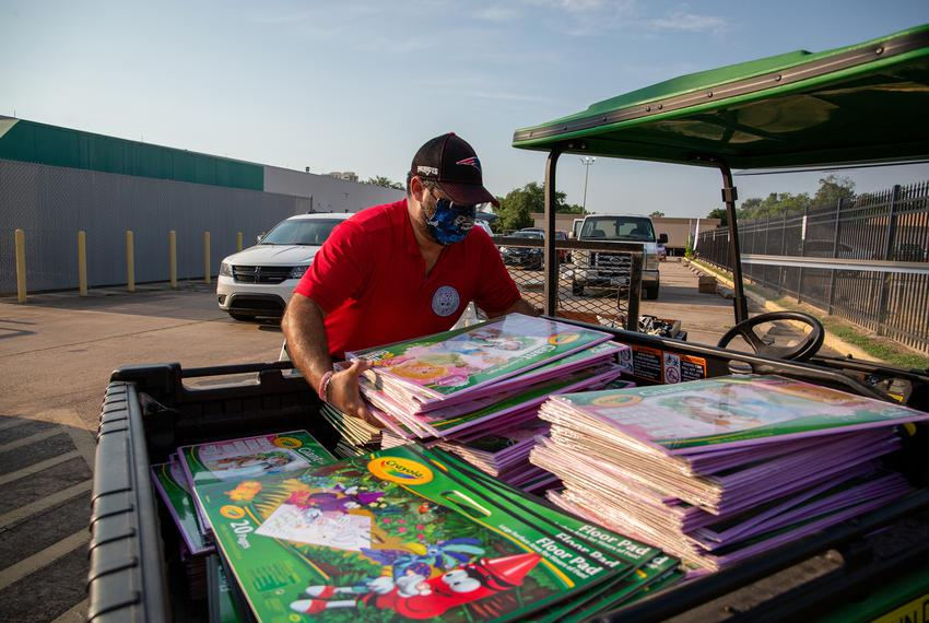 Supplies are loaded into vehicles during the Drive-Thru Student School Supply Giveaway at Raul Yzaguirre School for Succes...
