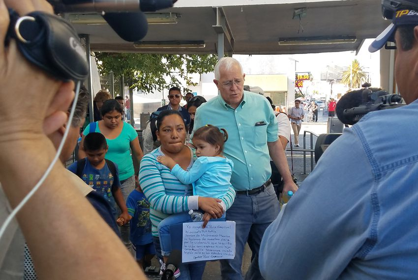 A group of American volunteers, led by Ruben Garcia, escorts a group of immigrants seeking asylum across the international bridge between El Paso and Ciudad Juarez.
