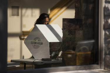 A voter casts their ballot at a polling site at the Austin Oaks Church on Oct. 14, 2020.