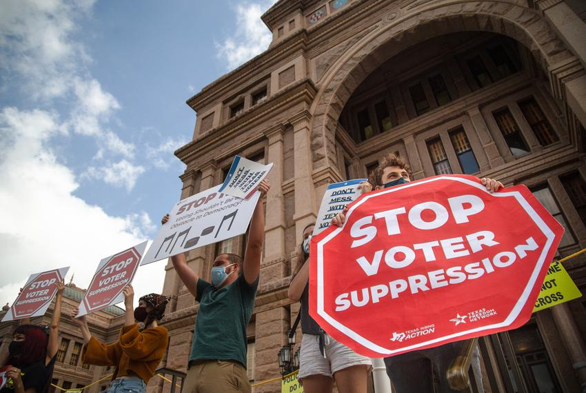 Protesters hold signs in opposition to SB 7 while participating in a rally at the state capitol on May 8, 2021.  Critics of …