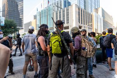 A man with a sniper rifle slung over his shoulder stands among protesters who have gathered at the Garrett Foster memorial in downtown Austin on Aug. 1, 2020.