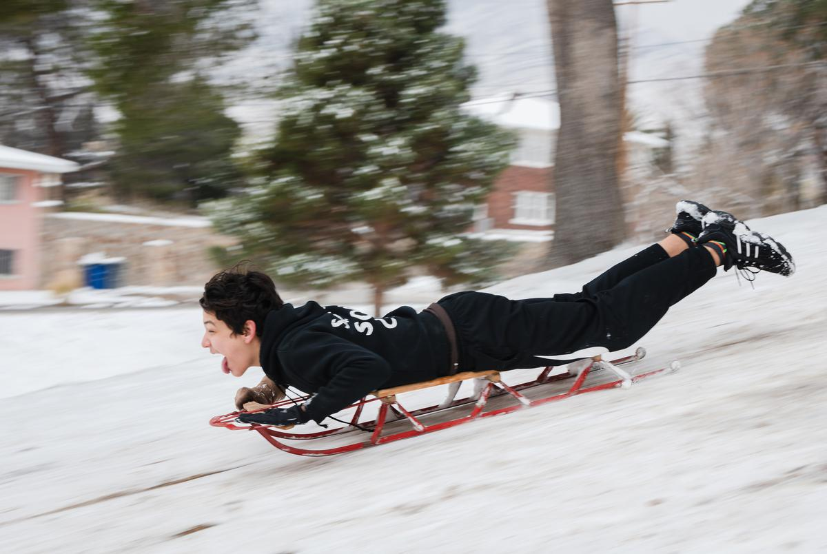 Logan Williams sleds down a hill at Memorial Park in El Paso, Texas on February 15, 2021.