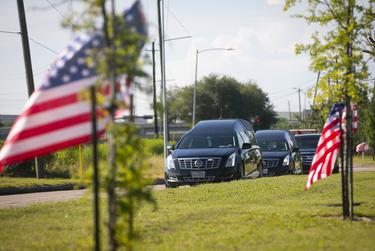 A hearse containing the body of George Floyd drives up a flag-lined street as it approaches the Fountain of Praise Church in Houston on June 8, 2020.
