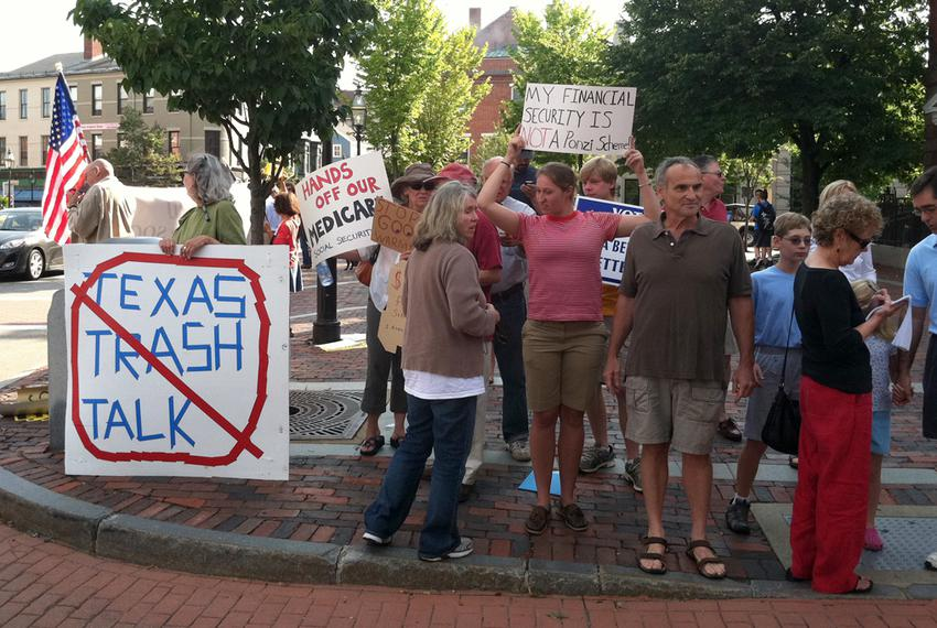Protesters in Portsmouth await Perry's arrival at Popovers restaurant Thursday, where the Texas governor will meet with vot…