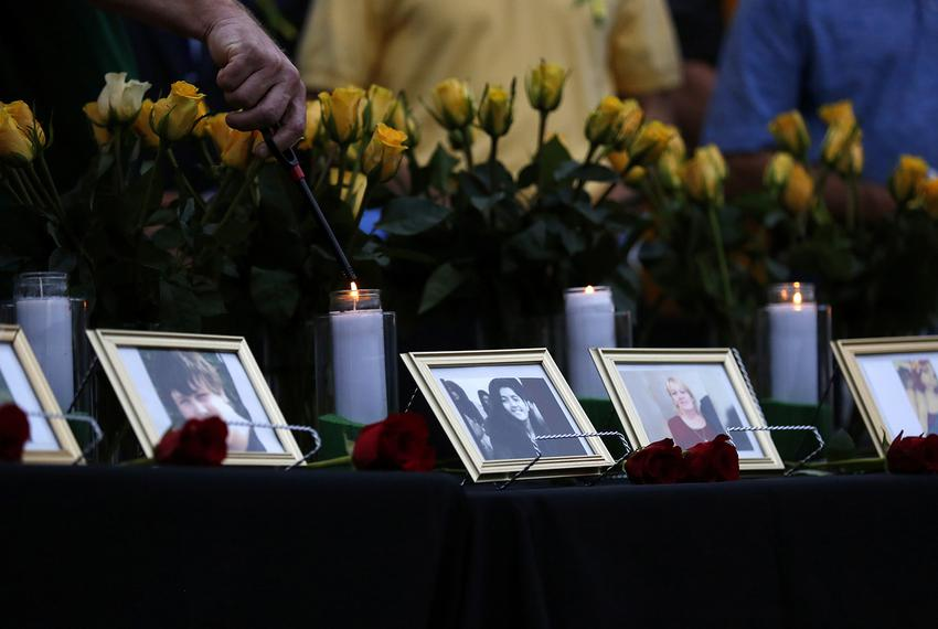 Candles are lit behind images of the victims killed in a shooting at Santa Fe High School during a vigil in League City on...