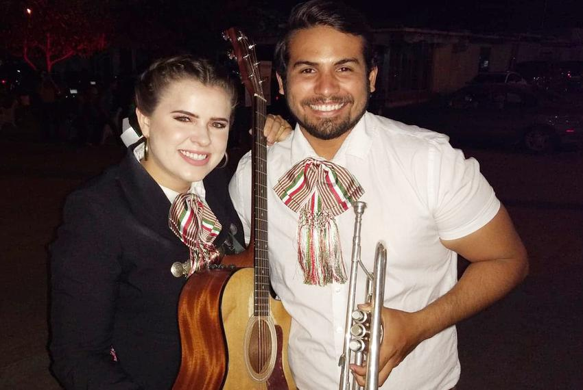 Molly Ferguson and Miguel Rodriguez pose with instruments in mariachi outfits as Ferguson's father, the mayor of Presidio, s…