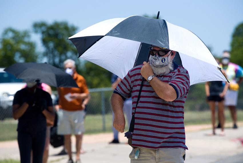 A voter uses an umbrella for protection from the sun. Voters waited in 100 degree temperatures outside the Pflugerville ISD …