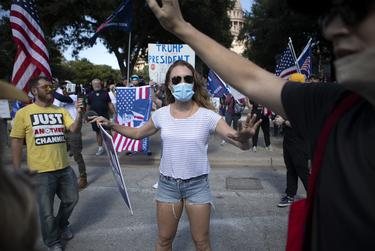 A supporter of President-elect Biden attempts to calm tensions as Trump and Biden supporters argued and yelled at each other near the state Capitol. Nov. 7, 2020.