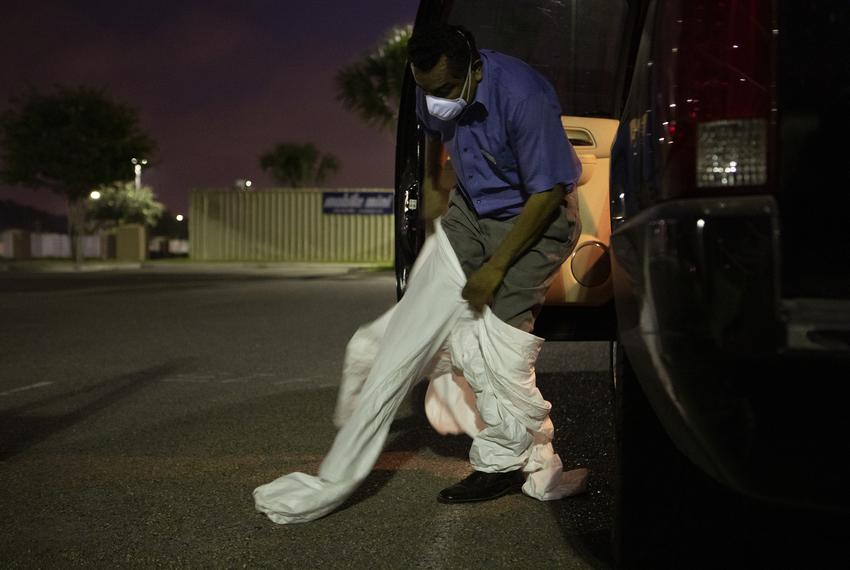 Juan Lopez puts on his personal protective equipment before picking up a body at Doctors Health at Renaissance in Edinburg...