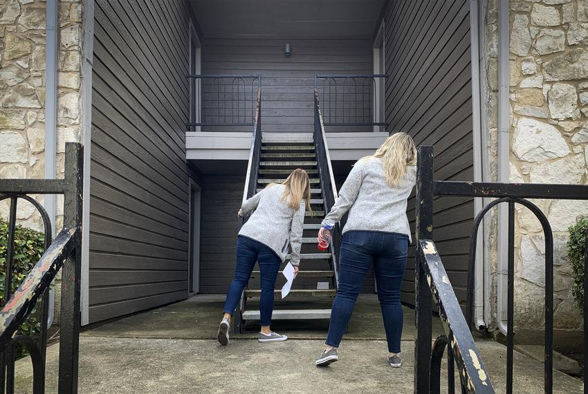 Brandee Brandt (left) and Emily Countryman look for apartment numbers at one of 15 stops they will make during a day of home…