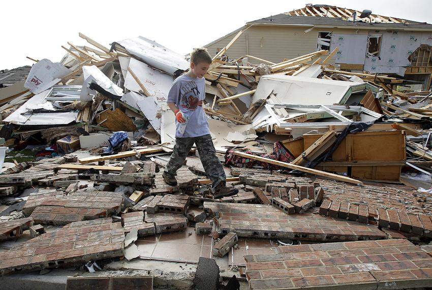 Duncan Winters, 10, walks through the remains of his grandmother's home during the cleanup effort in Forney on April 4, 2012…