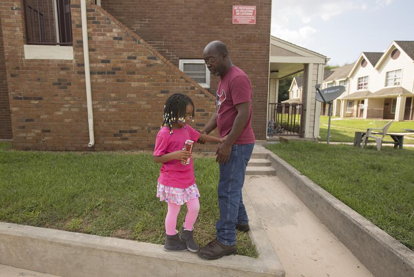 Eddie Rogers tries to convince his daughter Karla, 6, that there are no snakes near his apartment in Houston on Thursday, Au…