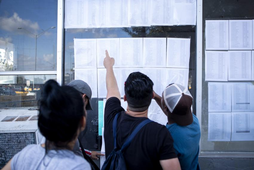 A group of Cuban migrants look at the list of asylum seekers near the Gateway International Bridge in Matamoros, Tamaulipas.