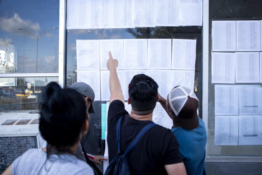 A group of Cuban migrants look at the list of asylum seekers near the Gateway International Bridge in Matamoros, Tamaulipas.