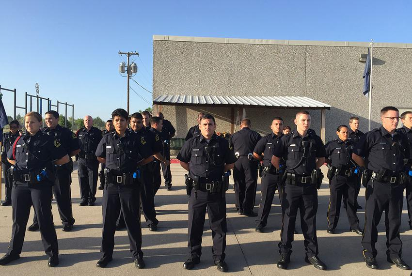 Dallas police academy recruits line up in formation. They'll complete a nine-month training course before going out on pat...