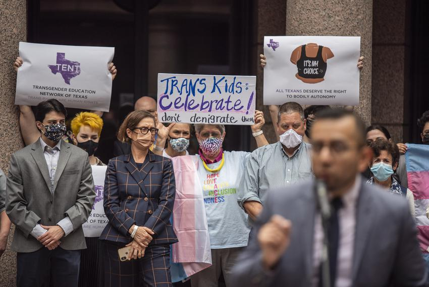 People hold up signs at an event held by Equality Texas at the Capitol on April 14, 2021. The group had several speakers inc…