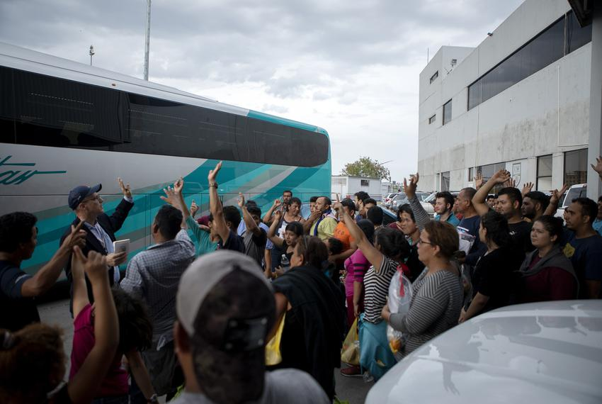 A group of migrants raise their hands after Texas Tribune reporter Jay Root asked how many planned on returning to Central A…