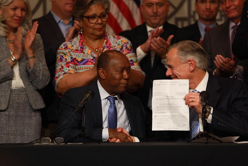 Gov. Greg Abbott presents Houston Mayor Sylvester Turner with a $50 million check for Hurricane Harvey relief during a news …